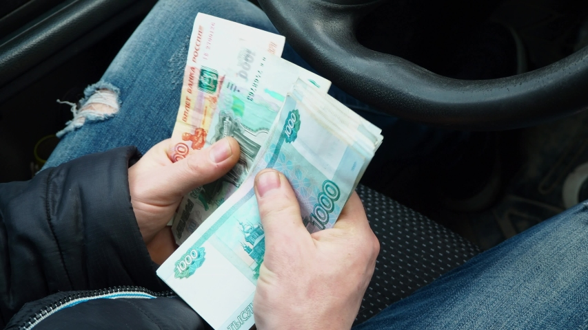 A man counts money. A lot of ruble banknotes in the hands of male. Salary of a Russian taxi driver. Purchasing a new car. A bribe to a traffic police inspector for violating traffic rules   Shutterstock HD Video #1052932067