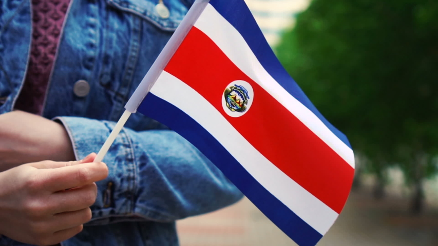 Slow motion: Unrecognizable woman holding Costa Rican flag. Girl walking down street with national flag of Costa Rica. | Shutterstock HD Video #1052932439