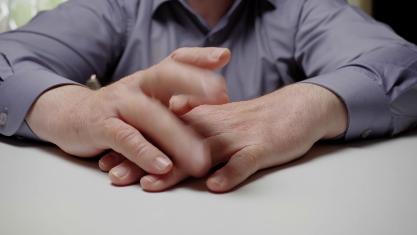 A nervous clerk or businessman is tapping his fingers on the table. Hands of a man in a gray shirt is knocking on the table, close-up | Shutterstock HD Video #1052938598