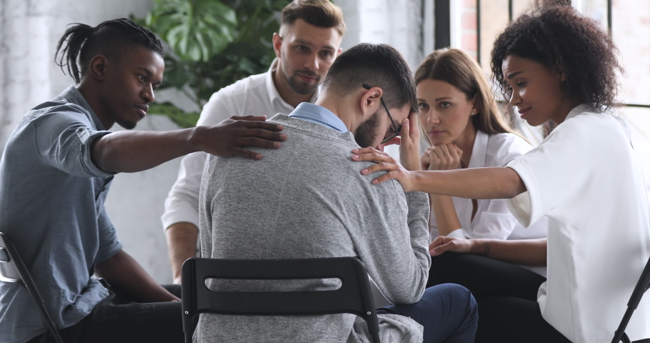 Young mixed race diverse compassionate people supporting desperate unhappy man. Depressed male patient suffering from bullying, sharing personal problems at psychological therapy group meeting.