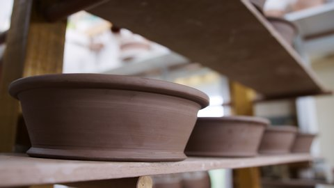 Group of handmade clay bowls on shelves of ceramics studio - shot in slow motion
