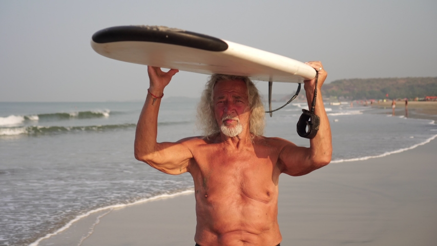 Strong healthy old man grandfather goes with a surfboard. Senior citizen with a surf | Shutterstock HD Video #1052946584