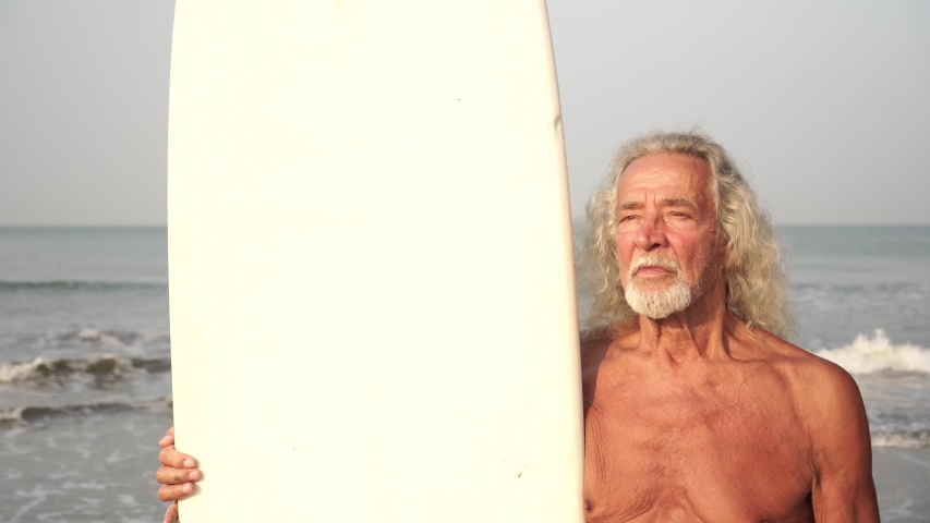 Portrait of an adult man, grandfather, old man with a surfboard on the beach | Shutterstock HD Video #1052946593
