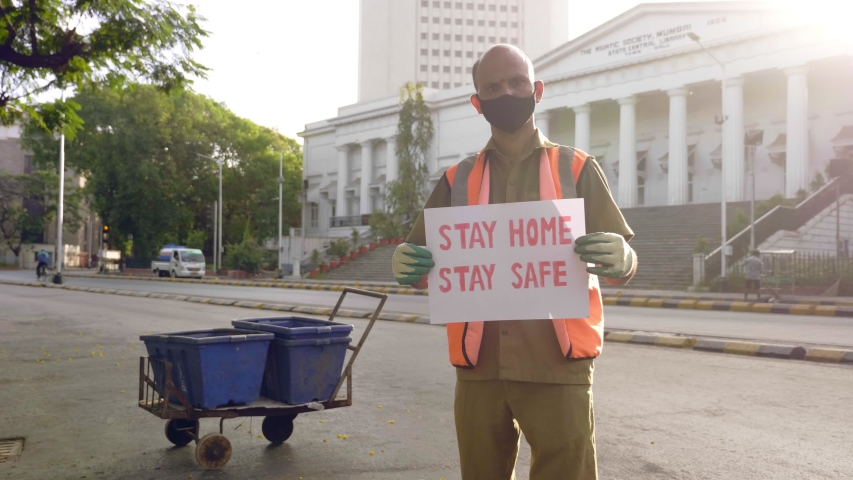 A male street sweeper essential service provider standing and holding a placard with message 'together we can stop Covid 19' during city lockdown amid coronavirus/ corona epidemic/ pandemic | Shutterstock HD Video #1052948444