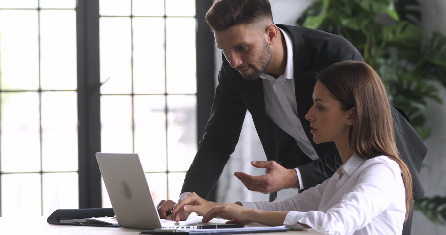 Side view confident company employee in suit standing near table, helping female colleague with corporate computer software. Young businessman discussing reviewing project with skilled manager. Royalty-Free Stock Footage #1052948801