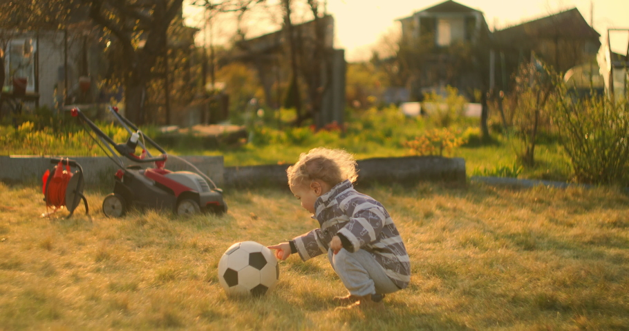 A little boy kicks a soccer ball with his foot in the field behind the house. A little football player in slow motion. Backyard. | Shutterstock HD Video #1052952296
