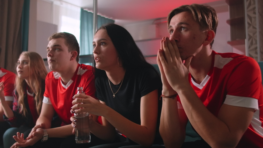 Group of fans are watching a soccer moment on the TV and celebrating a goal, sitting on the couch in the living room Royalty-Free Stock Footage #1052952308