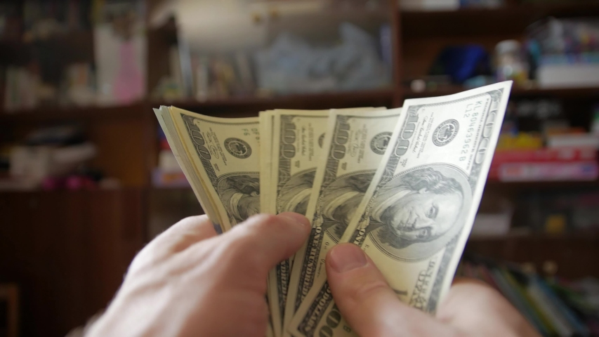 Fan of money 100 dollars bills banknotes POV point of view living room background camera movement mans hands | Shutterstock HD Video #1052953430