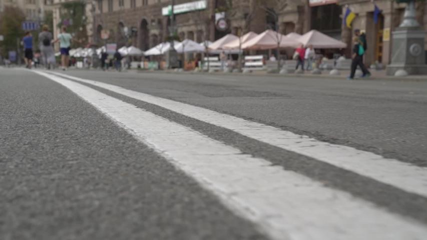 Road marking double line city street unrecognizable pedestrians camera movement slow motion | Shutterstock HD Video #1052953448