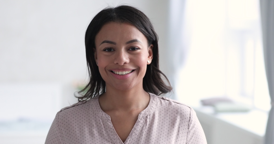 Head shot close up young smiling mixed race beautiful woman looking at camera indoors. Portrait of happy 30s african american lady with healthy smile, satisfied with dentistry whitening service.