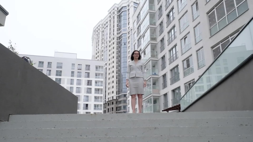 Successful business woman dancing and jumping for joy on the street. Beautiful girl in a business suit rejoices on the stairs. Slow motion.   Shutterstock HD Video #1052954081