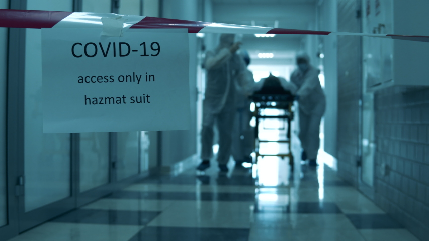 Paramedics are transporting a patient along the hall in lockdown. Covid-19 concept. Royalty-Free Stock Footage #1052956853
