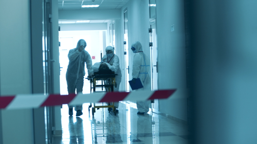 Paramedics are taking a patient through a hall under lockdown. Covid-19 concept. | Shutterstock HD Video #1052956865