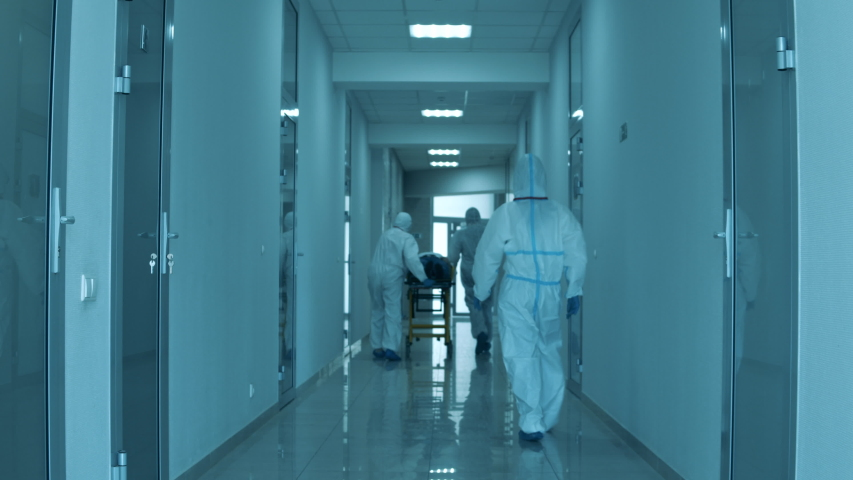Patient's transportation held by a group of doctors in safety suits Royalty-Free Stock Footage #1052956874