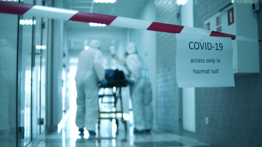 Quarantined corridor with doctors transporting a patient along it. Covid-19 concept. Royalty-Free Stock Footage #1052956943
