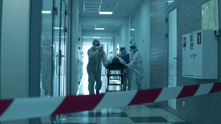 Paramedics are transporting a patient through the hospital during coronavirus pandemic. Royalty-Free Stock Footage #1052956949