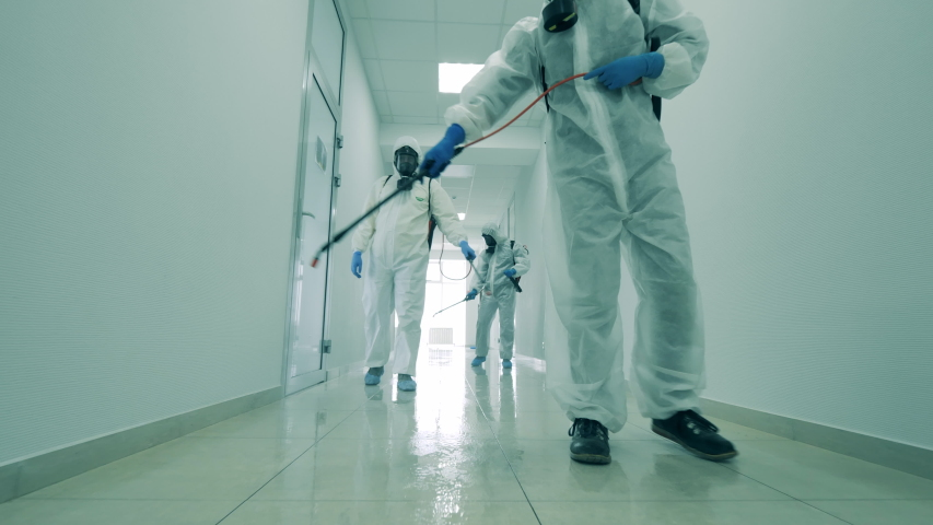 Group of specialists are sanitizing a white hallway Royalty-Free Stock Footage #1052956952