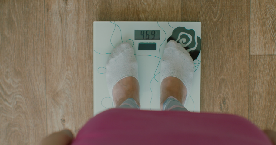 Close-up of a woman weighing herself on a scale at home. Close-up of a woman's feet on a scale, top view. | Shutterstock HD Video #1052957957