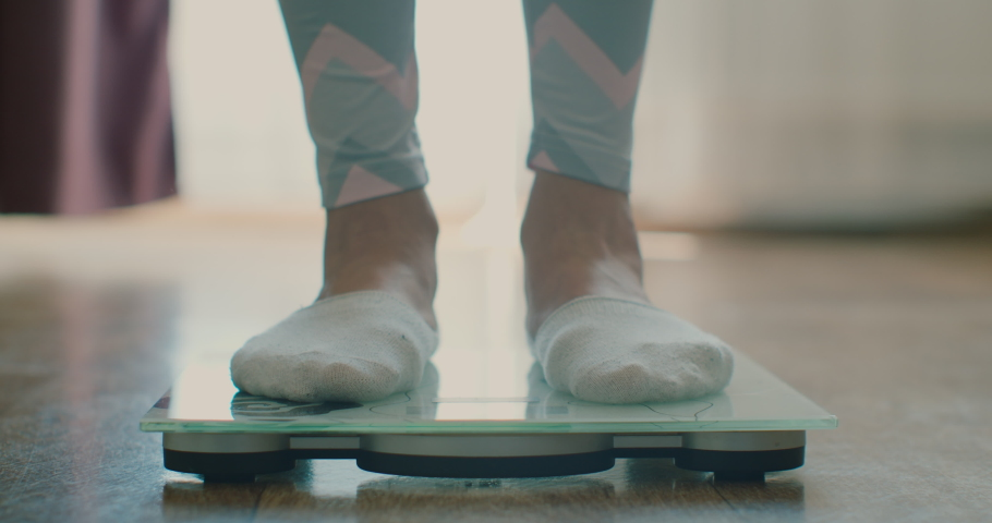 Close-up of a woman weighing herself on a scale at home. Close-up of a woman's feet on a scale. | Shutterstock HD Video #1052957978