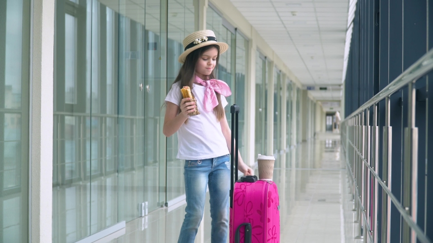 Little girl eat fast food and drink coffee at the airport while waiting for the plane. Flight delay | Shutterstock HD Video #1052958221
