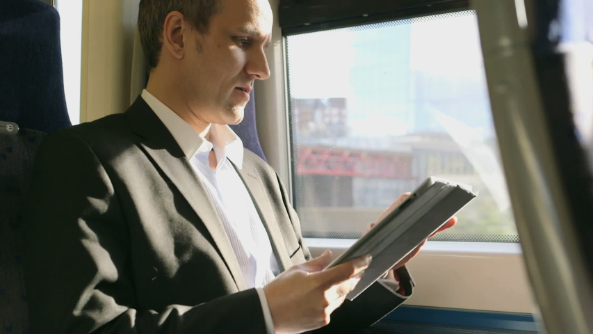 MS Business Man types into his digital tablet on a train Royalty-Free Stock Footage #1052960264