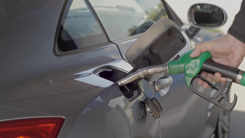 Close up of hand and fuel nozzle into automobile's tank. Fuel, gas station, petrol prices concept. Filling car with gas fuel at station pump.