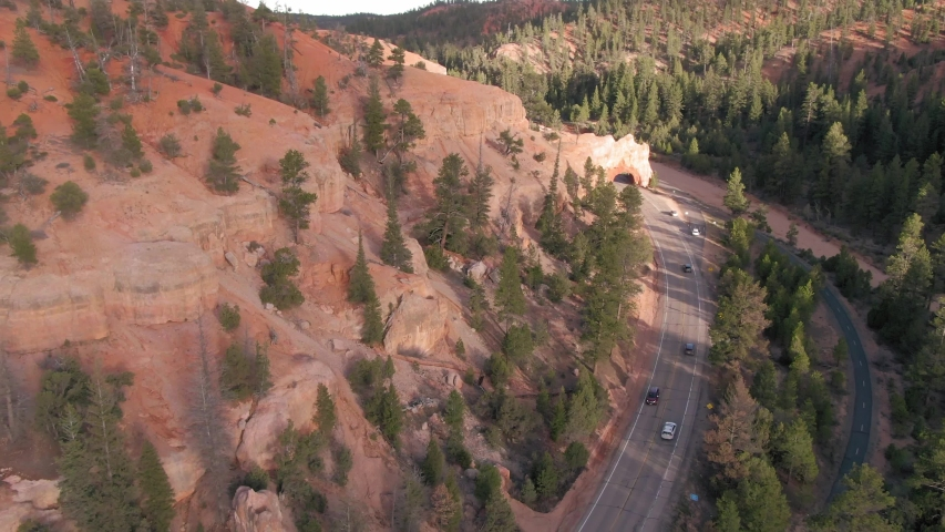 Aerial: Road & cars going through a rock tunnel in Red Canyon. Utah, USA