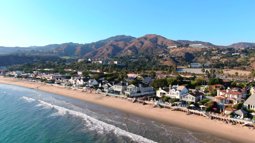 4K Aerial drone shot of Malibu Beach coastline in California with the blue Pacific Ocean with waves coming in and beach with nice houses on the background | Shutterstock HD Video #1052965268