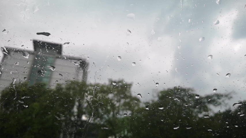 Rainwater drips down the car's windshield and the wiper moves to clear the rain while the car is in the parking lot | Shutterstock HD Video #1052967803