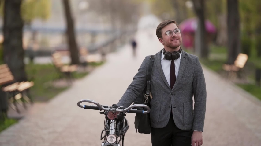 Handsome young businessman goes with bicycle in park and smiles | Shutterstock HD Video #1052970530