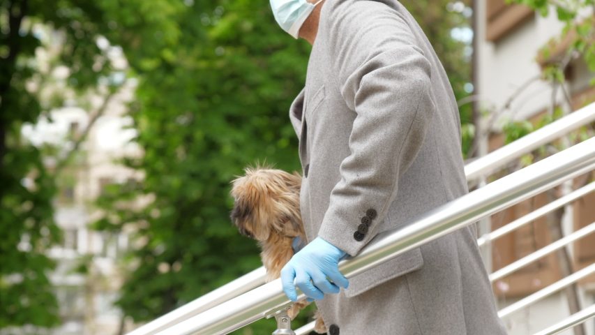 Man with damaged leg walks near stairs handrails holding dog in hand with sterile gloves. Concept social distancing   Shutterstock HD Video #1052972030