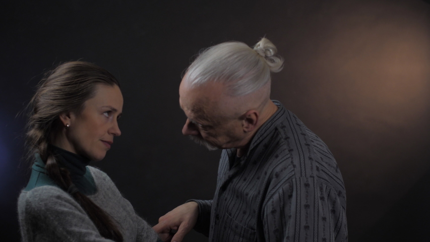Funny senior man with long grey mustache looks at angry dark haired woman eyes standing with crossed arms close view. People emotion   Shutterstock HD Video #1052972036