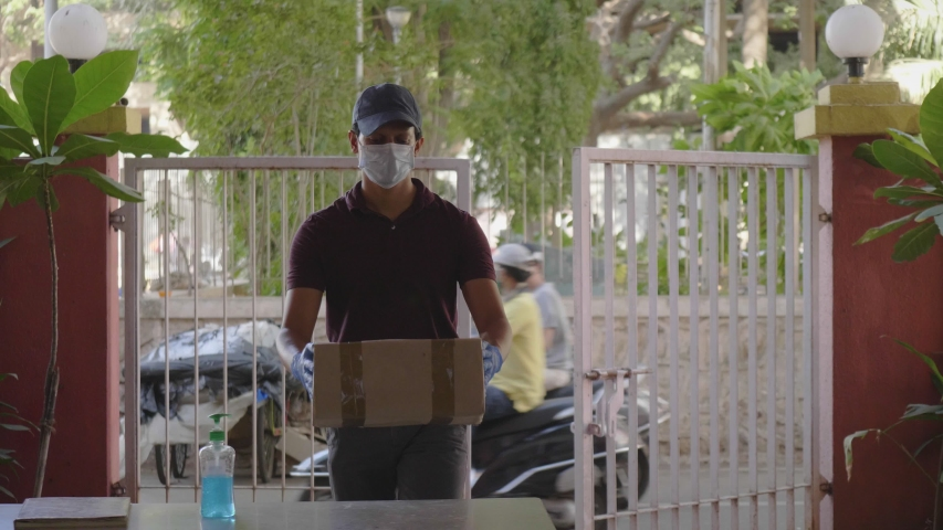 A delivery man or boy on wearing protective face mask delivers the box courier package on a building desk gate or doorstep during lockdown amid coronavirus or COVID19 epidemic or pandemic.