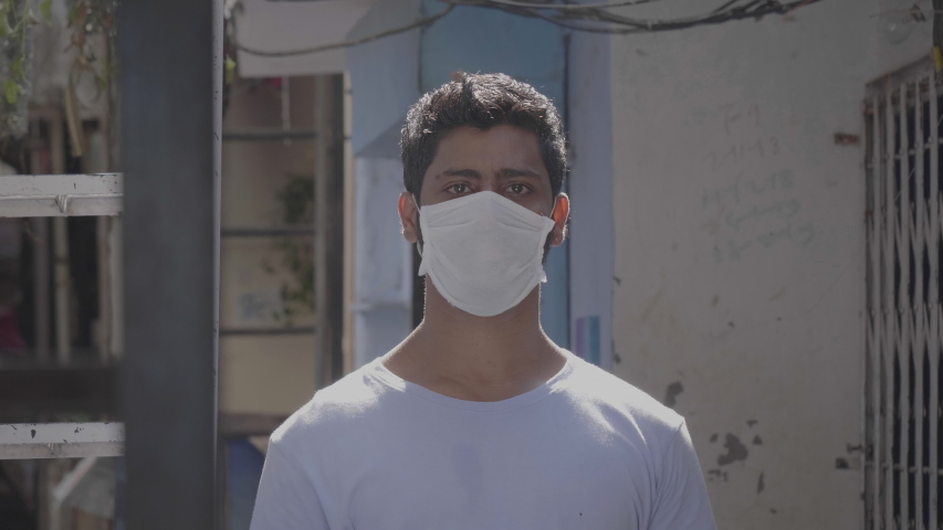 Close up shot of a young confident man wearing protective face mask looking in the camera amid coronavirus or COVID19 epidemic or pandemic | Shutterstock HD Video #1052973203