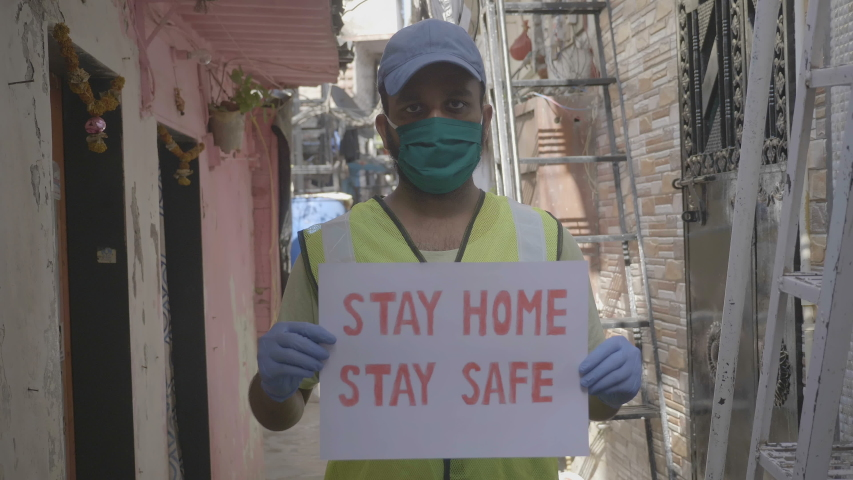A young man health worker or essential service provider wearing face mask holding a placard with message 'stay home stay safe' during lockdown amid coronavirus or COVID19 epidemic or pandemic  Royalty-Free Stock Footage #1052973206