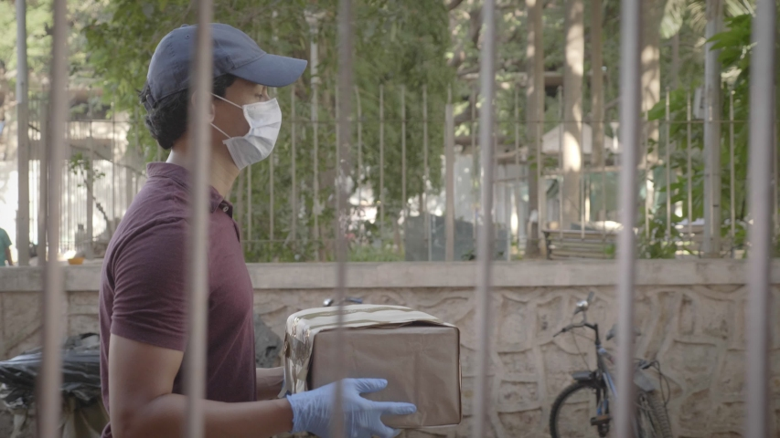 A delivery man or boy on wearing protective face mask walking with courier package on a the road or street during lockdown amid coronavirus or COVID19 epidemic or pandemic. Royalty-Free Stock Footage #1052973209