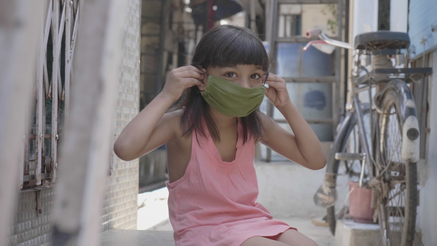 A close shot of cute young little girl child wearing or putting a face mask while sitting outside in the lane amid coronavirus or COVID19 epidemic or pandemic Royalty-Free Stock Footage #1052973212