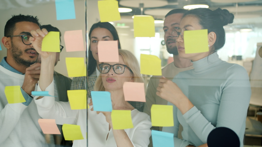 Colleagues multiracial team are working with sticky notes on glassboard busy with problem solving focused on creative activity. People and strategy concept.