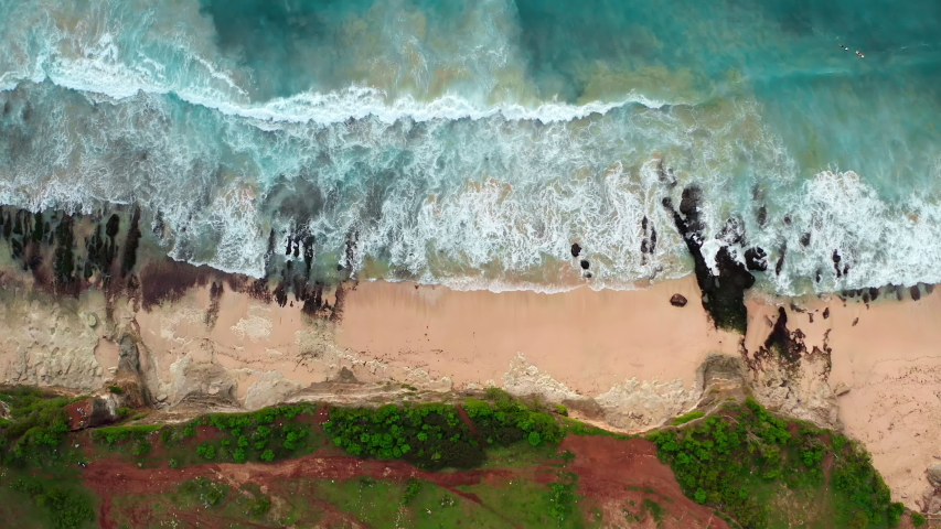 Aerial top view of ocean blue waves break on a beach. Sea waves and beautiful sand beach aerial view drone shot. Bird's eye view of ocean waves crashing against an empty sand beach from above.
