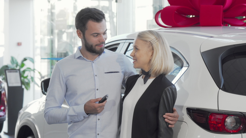 Happy young couple standing near their new car at the dealership. Handsome man and his wife celebrating buying new auto, holding car keys, smiling to the camera. Family, transport concept