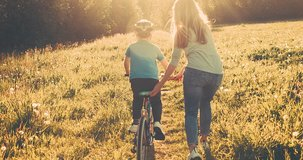Mother teaching son to ride bicycle. Happy cute boy in helmet learn to riding a bike in park on green meadow in summer day at sunset time. Family weekend. 4K video Slow motion