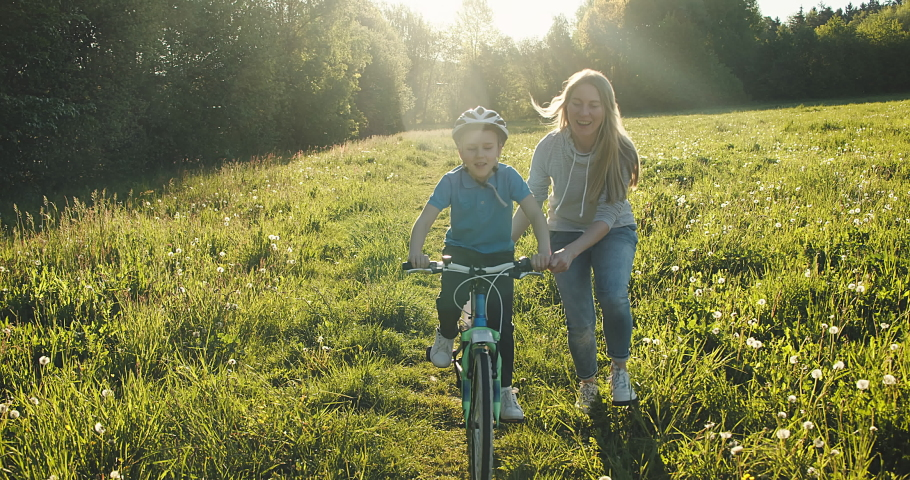 Mother teaching son to ride bicycle. Happy cute boy in helmet learn to riding a bike in park on green meadow in summer day at sunset time. Family weekend. 4K video Slow motion Royalty-Free Stock Footage #1052985236