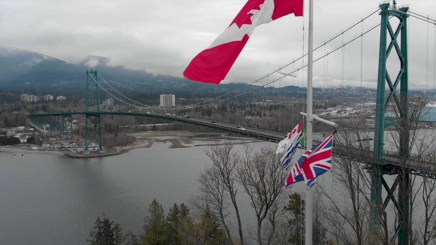 Slow motion Canadian flag waving at Prospect Point in Stanley Park with the Lions Gate Bridge in the background in Vancouver, BC. 4K 24FPS. | Shutterstock HD Video #1052989175