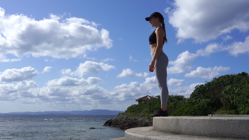 Young athletic woman is exercising outdoors. morning exercises. running on the stairs, jogging along the ocean, warming up and stretching against the blue sky on a sunny day.