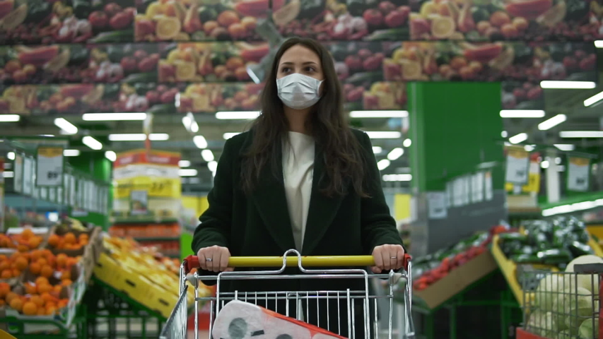 Woman in medical face mask buys basic necessities, hygiene items and food. Girl walks through empty supermarket or grocery store. Quarantine and self-isolation, epidemic covid-19, coronavirus pandemic Royalty-Free Stock Footage #1052993636