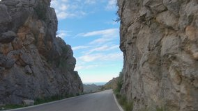 4K point of view footage of card driving through beautiful rocky mountain landscape. Scenic shot during evening time. Famous winding road in Serra de Tramuntana, Mallorca, Spain. Slow motion video