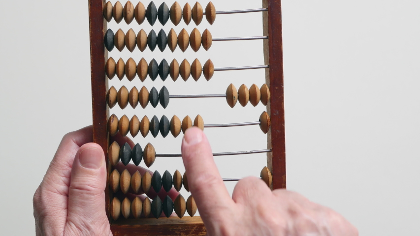A Elderly Man Is Holding And Moves Wooden Knuckles On A Outdated Vintage Wooden Abacus On A White Background, Close-up. .