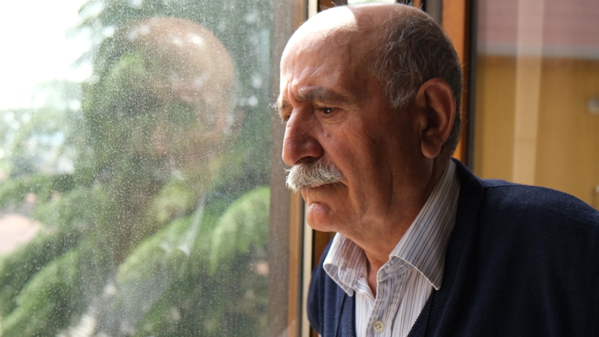 Closeup senior man looking to outside from window 4k