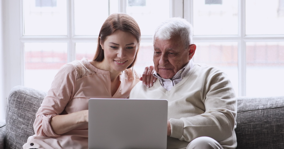 Smiling young attractive woman discussing internet shopping with older mature father, looking at computer screen. Happy grownup daughter showing technology application on laptop to old daddy at home.