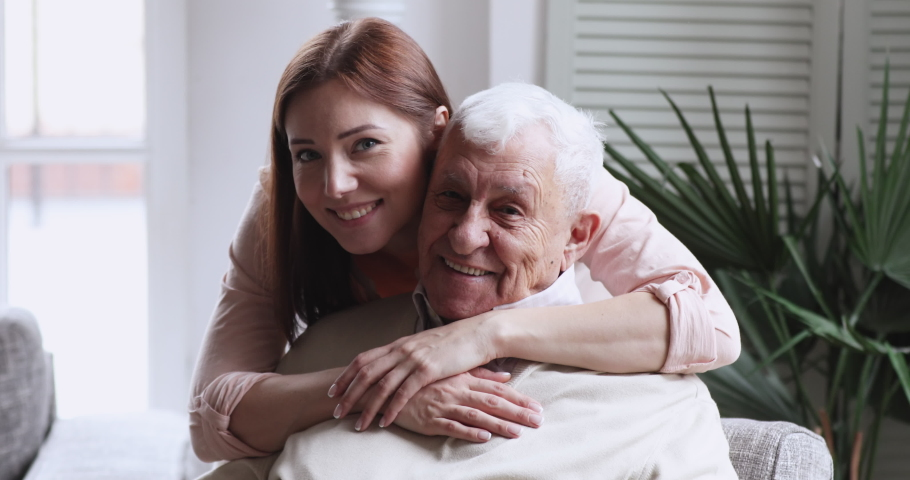 Smiling beautiful grownup daughter cuddling happy middle aged older father, head shot close up. Happy different generations family looking at camera, enjoying sweet tender moment together indoors.